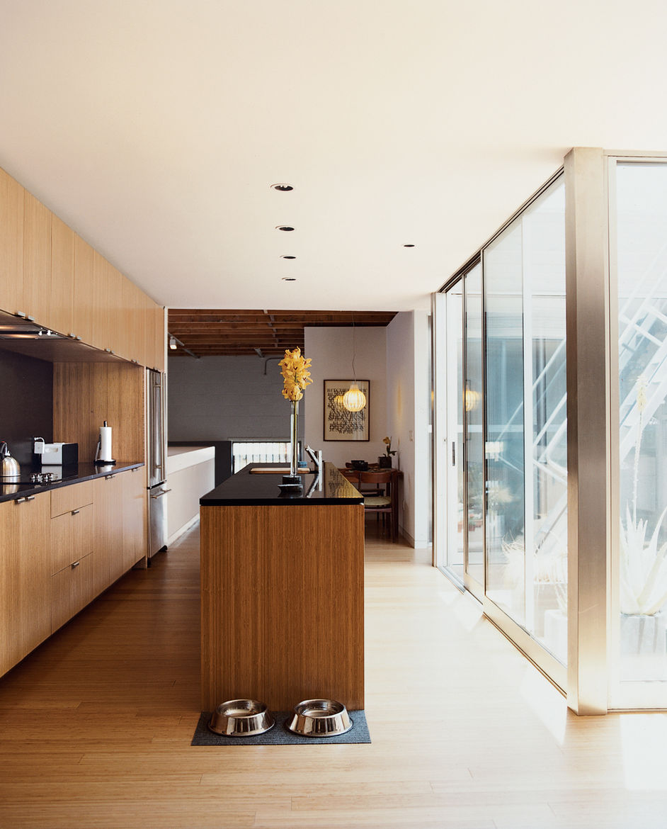 """The kitchen, with Richlite counters and upper cabinets that reach to the ceiling, leads to a small dining area illuminated by a Plexiglas """"Agave"""" lamp."""