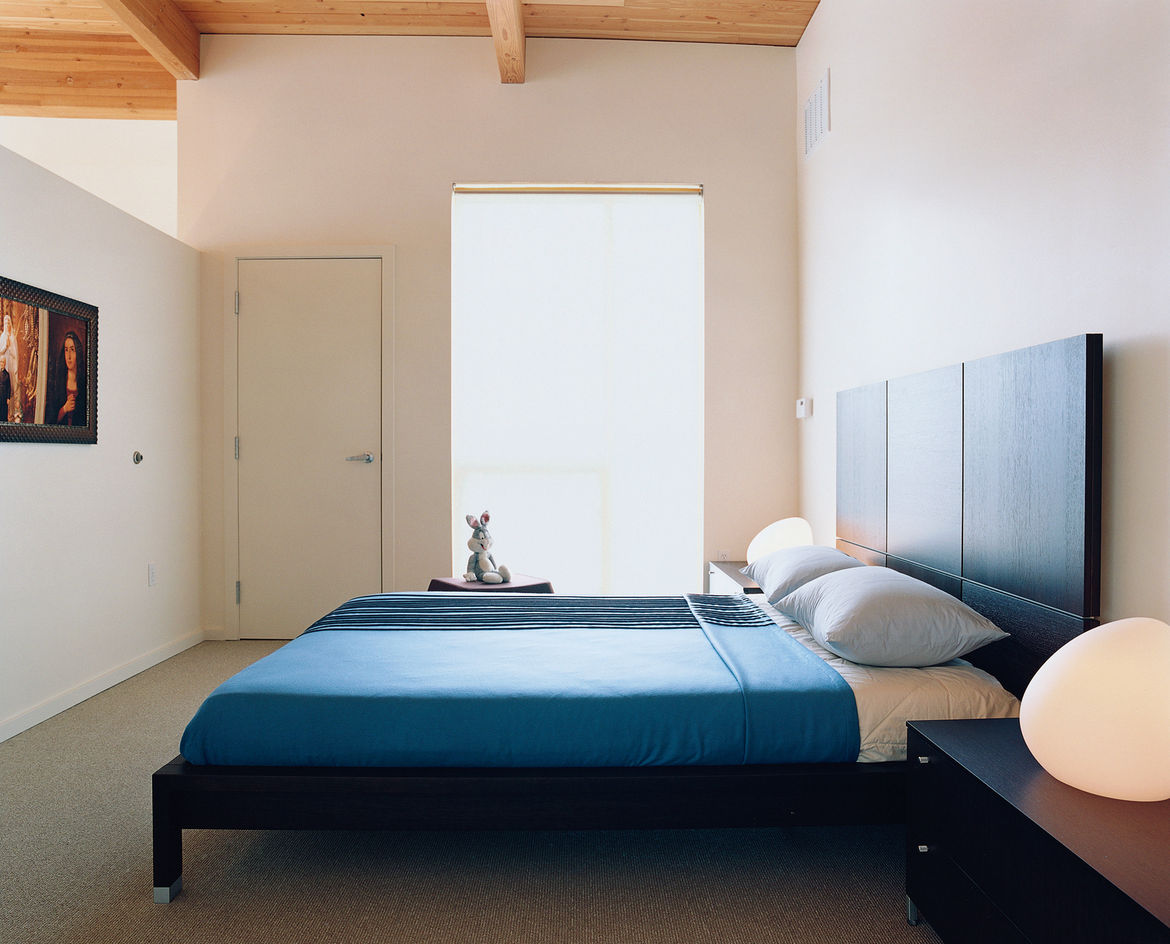 The simple, spare bedroom is brought to life by Rapaport's toy Bugs Bunny and a pair of egg-shaped Dolmen table lamps designed by Philippe Daney for Ligne Roset. The Lumeo bed is also by Ligne Roset and was designed by Peter Maly.