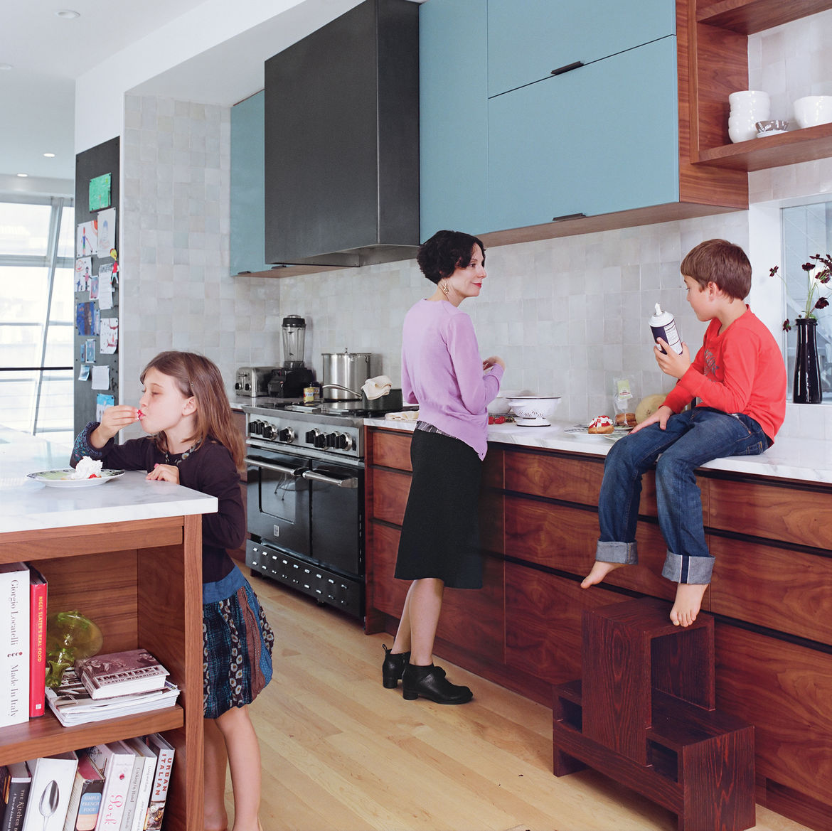 Sasha samples berries at the island while Wes, perched on the counter next to Deborah, clutches the whipped cream—similar in color to the backsplash, made of traditional Moroccan tiles and available through Emory & Cie.