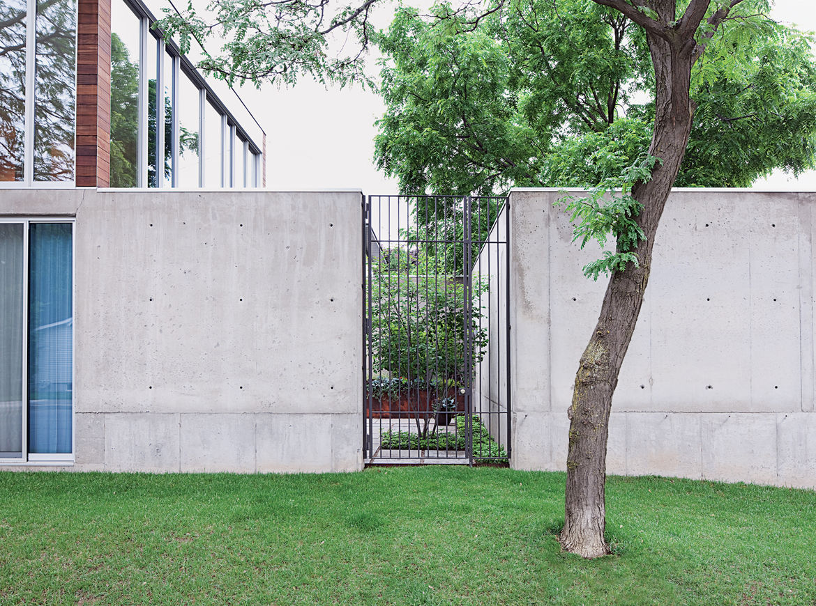 A tall steel gate grants entry to the courtyard.