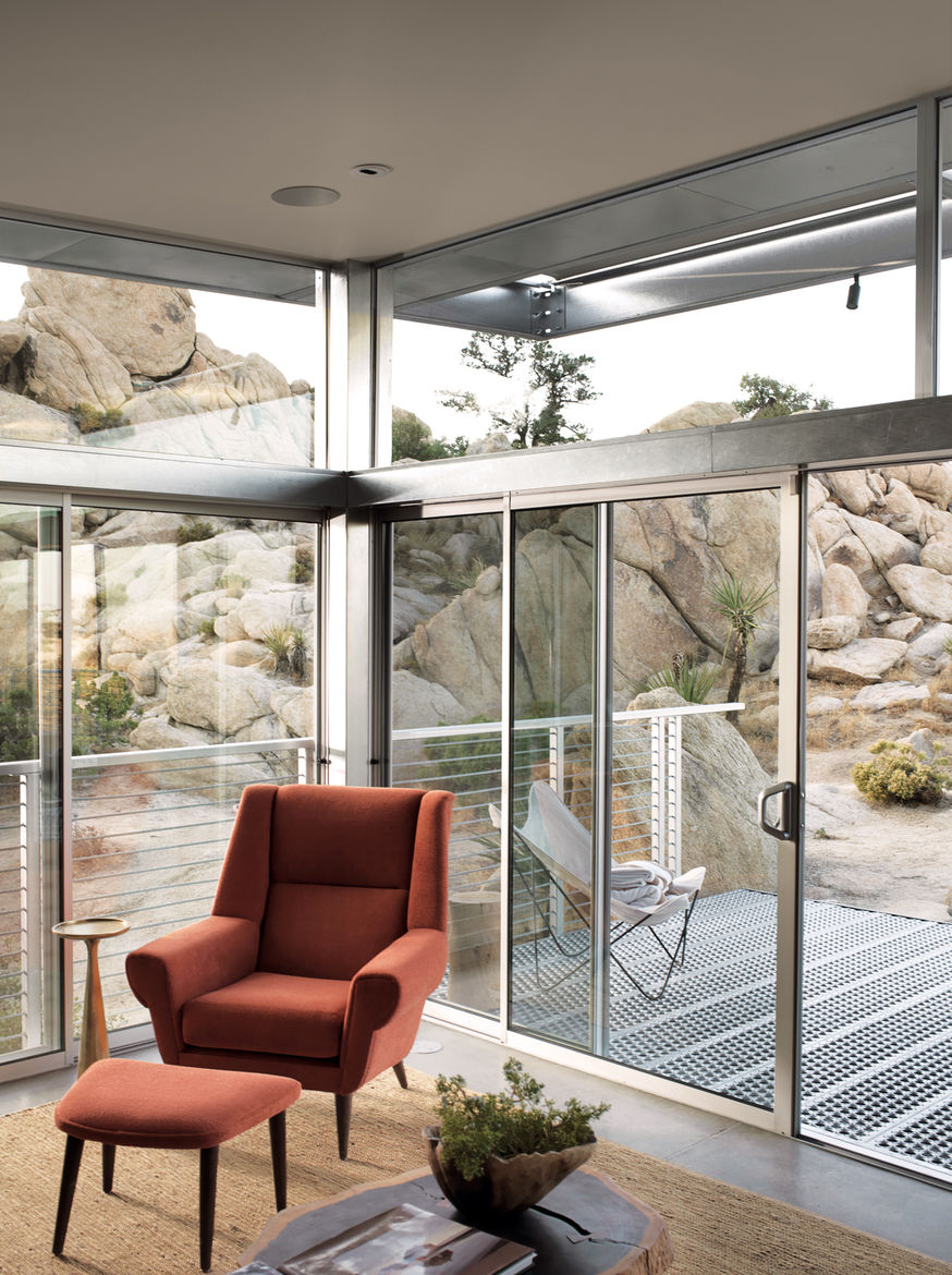 """The main living area extends to the deck through sliding glass doors. The orange David Chair and ottoman were designed by Palm Springs-based interior designer <a href=""""http://www.christopherkennedy.com"""">Christopher Kennedy</a> and are from his eponymous l"""