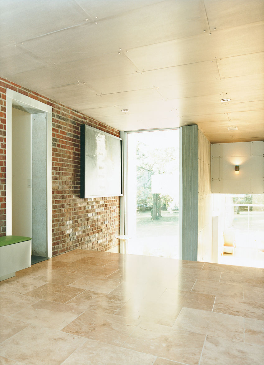 An area that once led from the original house to the garage is now enclosed and serves as a transitional space between the private and public areas of the house.