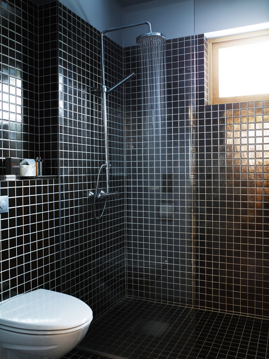 Simple black tiles and a basic, exposed showerhead kept costs down, allowing other parts of the house to function as the showpieces.