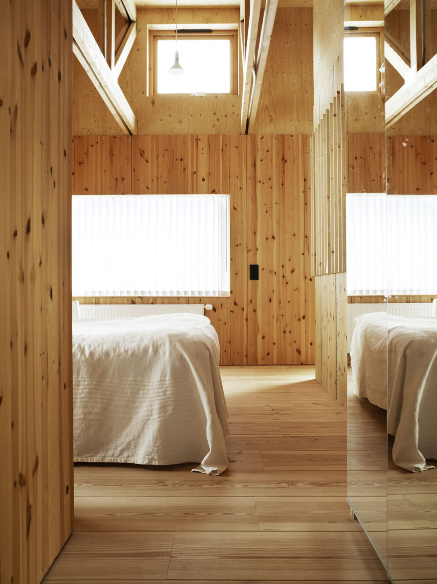 The white linens appear almost ghostly against the natural grain of the wood and muted glow of the window's winter light.
