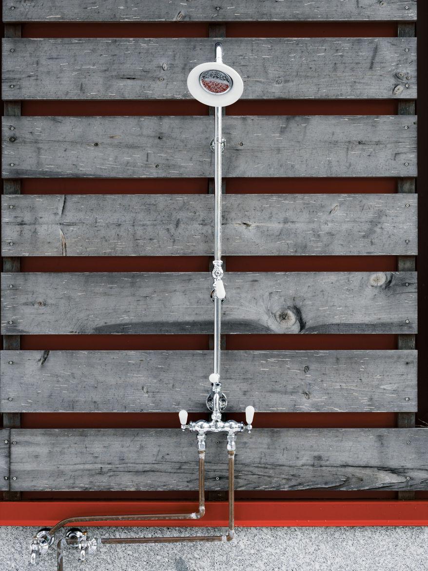 A stop at the outdoor shower reveals the red steel frame beneath the wooden siding.