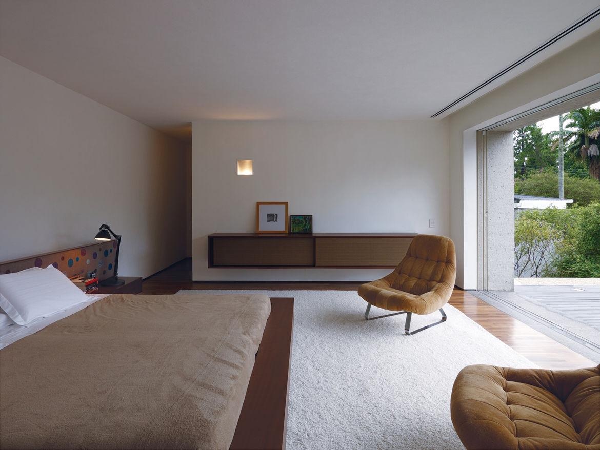 Kogan designed a number of the built-in furnishings, including the headboard and cupboard in the master bedroom.The cupboard is deliberately reminiscent of a mid-century stereo speaker. The vintage lounge chairs are by Percival Lafer.