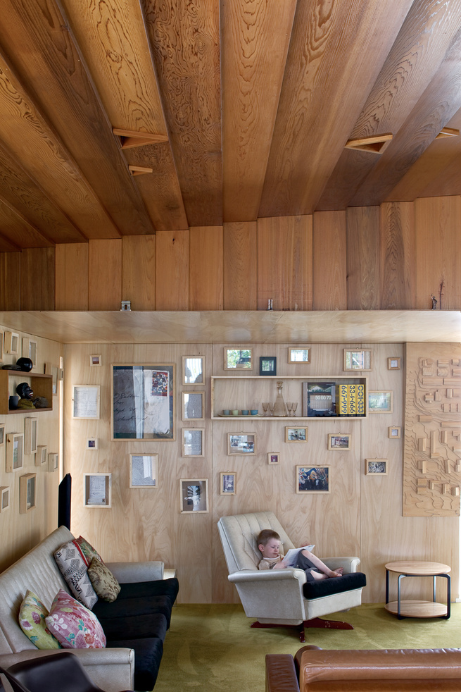 Four-year-old Seamus relaxes in the living room, whose plywood walls  are covered with family photographs.