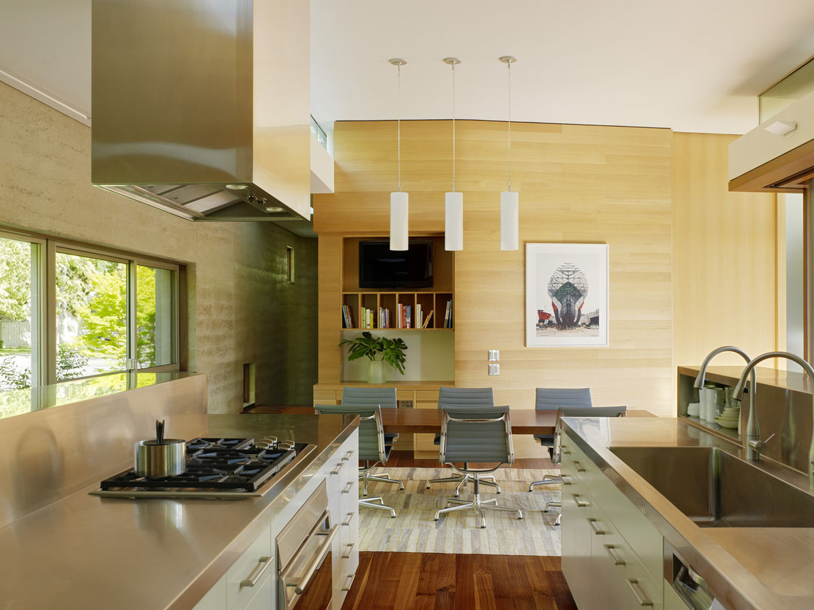 """Open spaces were very important to the close-knit family of five and the kitchen/dining area is one of their favorites in the house. The stainless steel countertops and hood were fabricated by American Metal Products out of San Francisco. """"We spend a lot"""