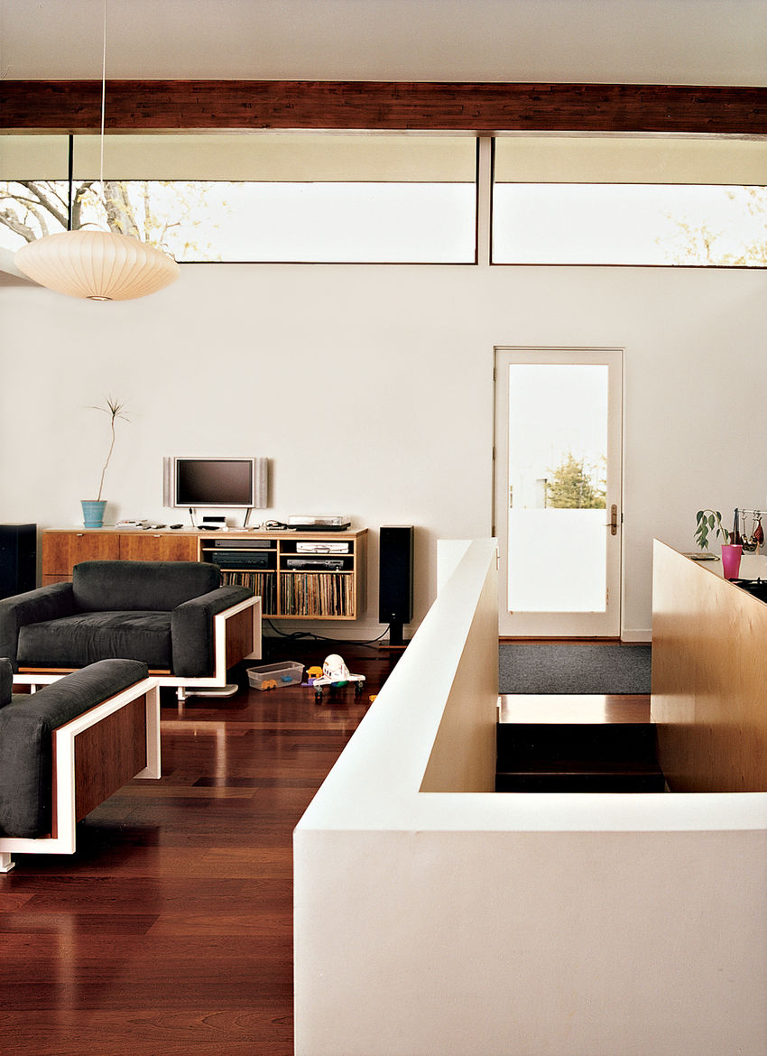 In the main living space, stairs lead to the basement. The white-framed chairs and couch were built by Jamie; the cabinets were designed by Jamie and built by a local cabinetmaker. Brazilian cherry floors run throughout the main house. The clerestory wind