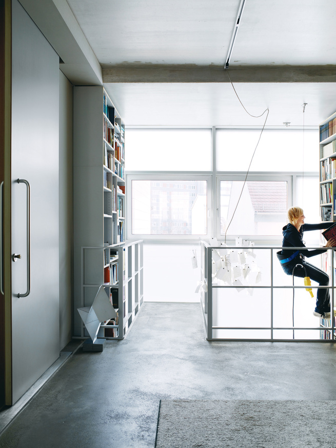 Dulkinys uses the remote-controlled mountaineer's harness to peruse the two-story bookshelf.
