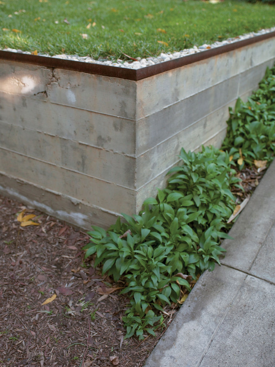 Concrete retaining walls form an outdoor terrace that serves as a dining area, conference room, and workshop. The three-quarter-inch construction gravel from George L. Throop Company allows rain to percolate into  the ground and irrigate a lemon tree rath
