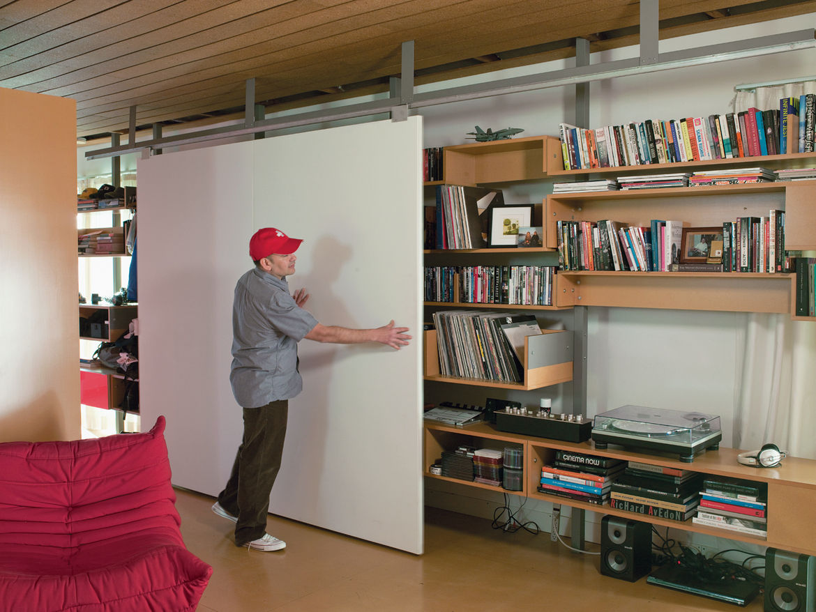 Molina and Turin combined angle and bar aluminum from Industrial Metal Supply Company and wheels from Pro-Fit Cabinet Hardware to  design a custom track for a sliding door/projection screen fashioned  out of two hollow-core doors from Stock Building Suppl
