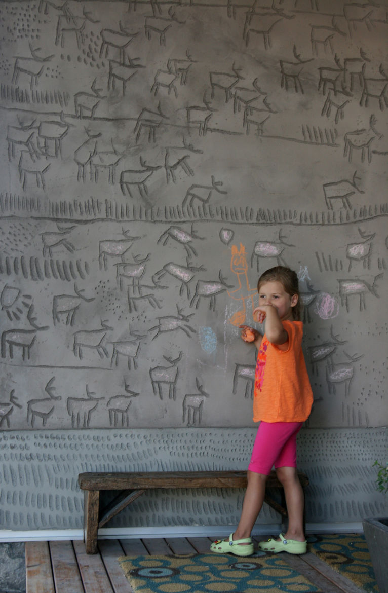 """The couple's daughter, Kalyna, puts her own spin on her father's engravings, which he calls a """"concrete coloring book."""" Dedicating this side of the building to the earth, he carved herds of caribou into the panels. The abstract marks at the base skirt the"""