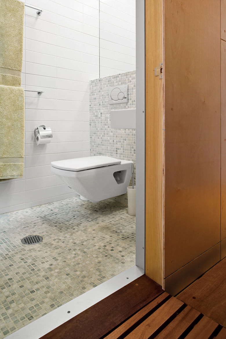 A skylight in the compact bathroom opens the space, and green tiles give the room a spa-like feel.