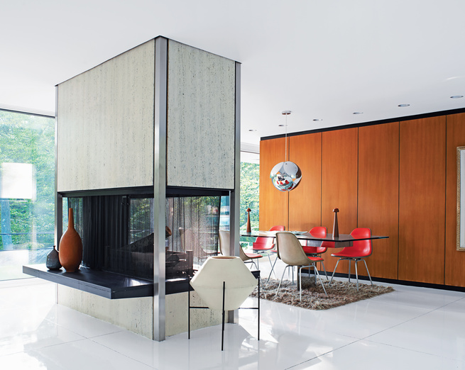 """""""On a bright day, you have to wear sunglasses in here,"""" Mandolene says. A freestanding travertine-and-steel fireplace, open on all four sides, divides the living and dining areas."""