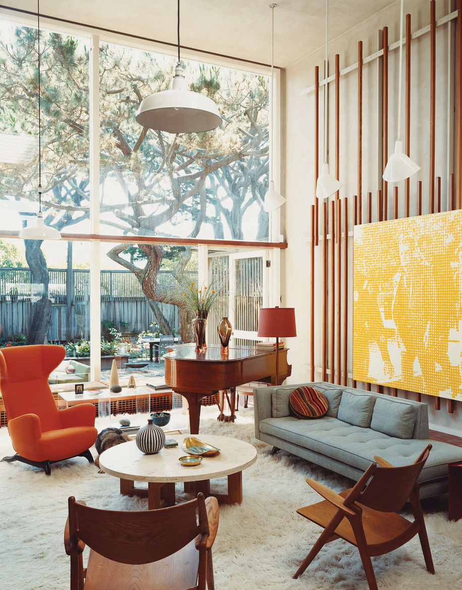 Born outfitted the living room of the original house with vertical slats on which to mount any manner of visual material. Artwork becomes easy to move around, but Lloyd-Butler likes the placement of a painting by Wayne Gonzales depicting Lee Harvey Oswald