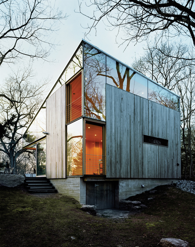 """Sheets of unframed glass fill the spaces between the building's operable windows and the sloping eave of the roof, giving the house, as architect Alan Organschi puts it, """"the feel of coming apart at the seams—of surfaces unhinged."""""""