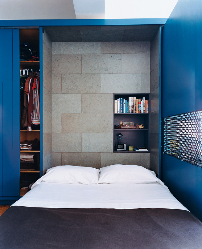 The interior of the Murphy bed compartment is lined with a stained cork panel and contains a smaller shelving unit for bedside reading, alarm clock, and reading lamp.