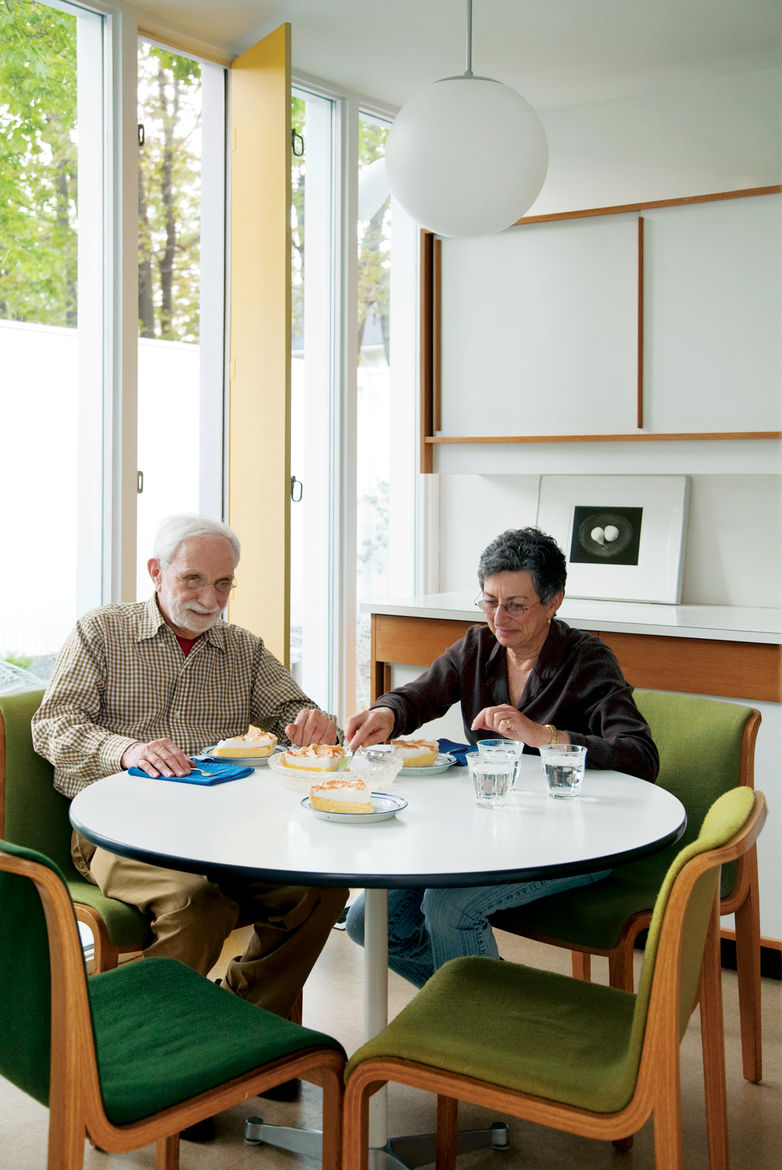 Isaacson and his best friend, Mary T. Hatch, snack at a dining table by Charles and Ray Eames for Herman Miller in the eat-in kitchen.