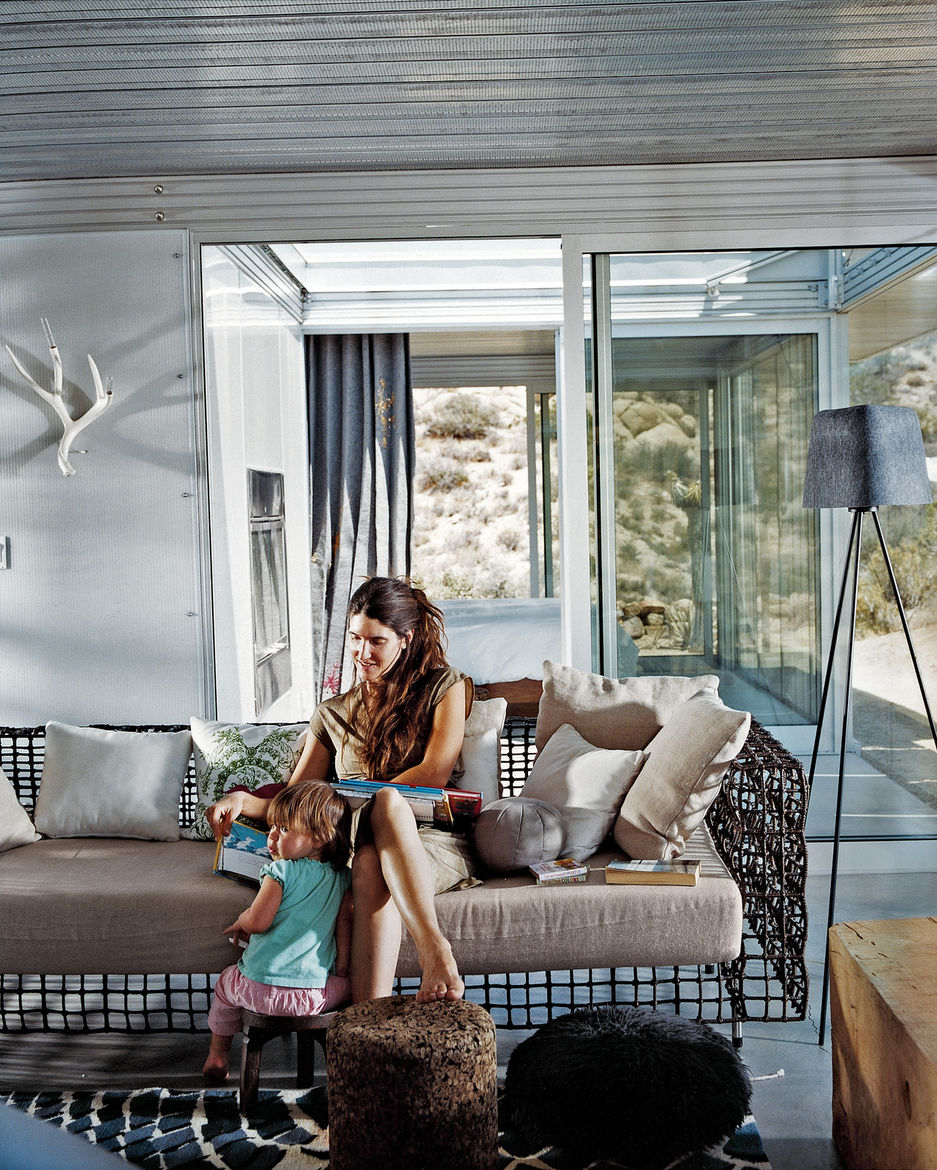 Taalman sits with their daughter, Oleana, in the living room on a metal lounge designed by Kenneth Cobonpue. Glass walls emphasize views and greatly expand the sense of space in the 1,100-square-foot house. Through the glass wall behind her is the fire co