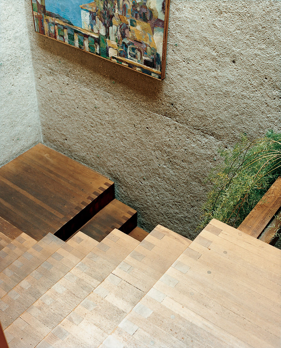 Rail-free stairs are unnerving for a first-time visitor, but they amplify the home's free-flowing sense of space and structure. The stairs were built inside one of the six concrete towers, and they lead from the central living space to the front door. The