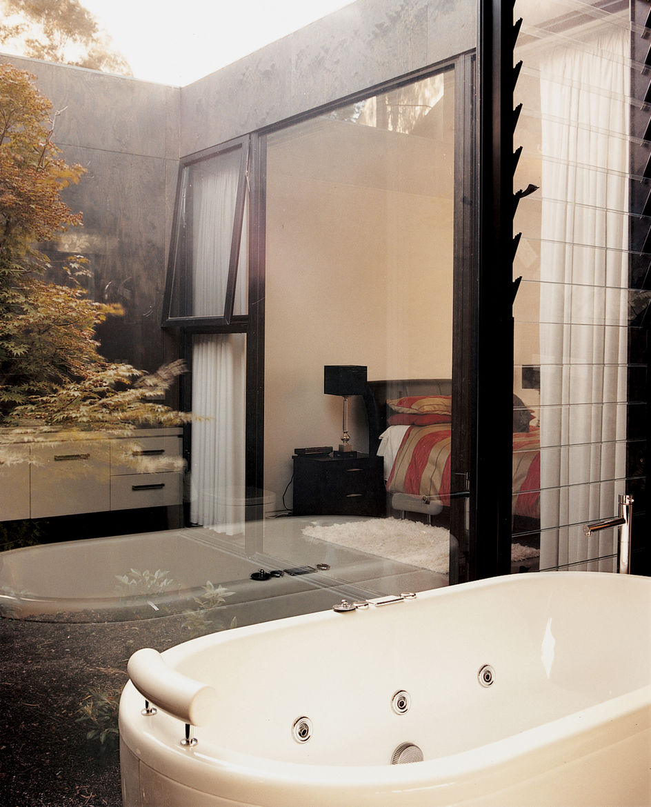 """The guest bathroom  includes glass walls that look out onto one of the house's """"voids,"""" in which pear trees grow."""
