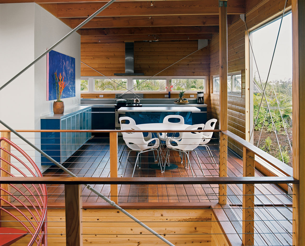 The home's upper floor features copious amounts of untreated pine. Five large cross-braces keep the timber frame rigid. The royal blue Ikea kitchen, Noguchi Cyclone dining table for Knoll, and Karim Rashid Oh chairs for Umbra all made the trip from the ma