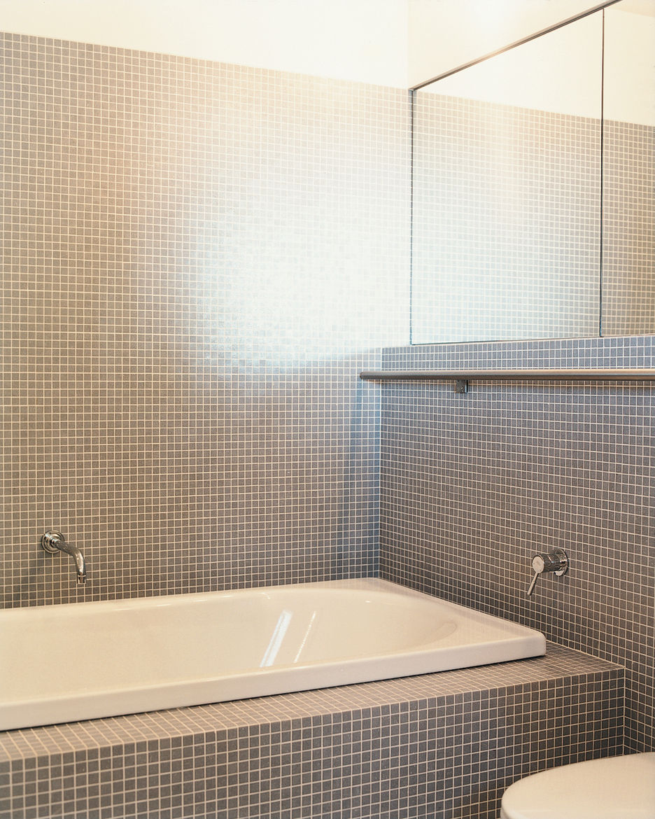 A stainless-steel towel bar runs the length of two walls in the master bathroom.