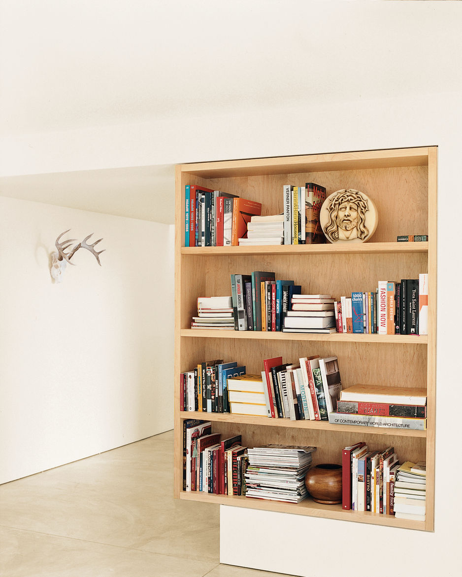 A maple bookcase defines the point between the living room and foyer.