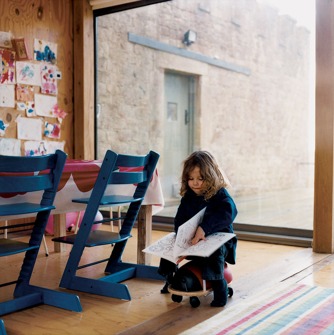 The main living room is an open-plan space with an integrated kitchen and dining area. The table, made by Taylor and shrouded in Marimekko, is outfitted with blue Tripp Trapp adjustable children's chairs by Stokke; the striped rug is from Ikea.