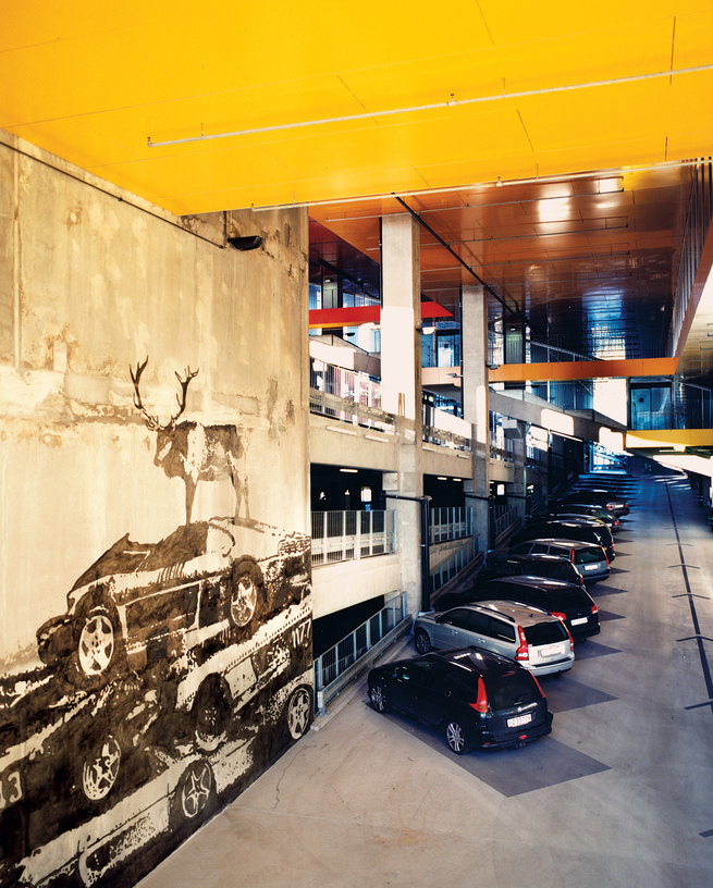 """Not content to just build a regular parking lot behind the Himalayan facade, Ingels created a high-ceilinged, five-story, concrete-and-steel """"car cathedral—to celebrate car culture."""" Throughout, the French artist Victor Ash varnished the concrete walls wi"""