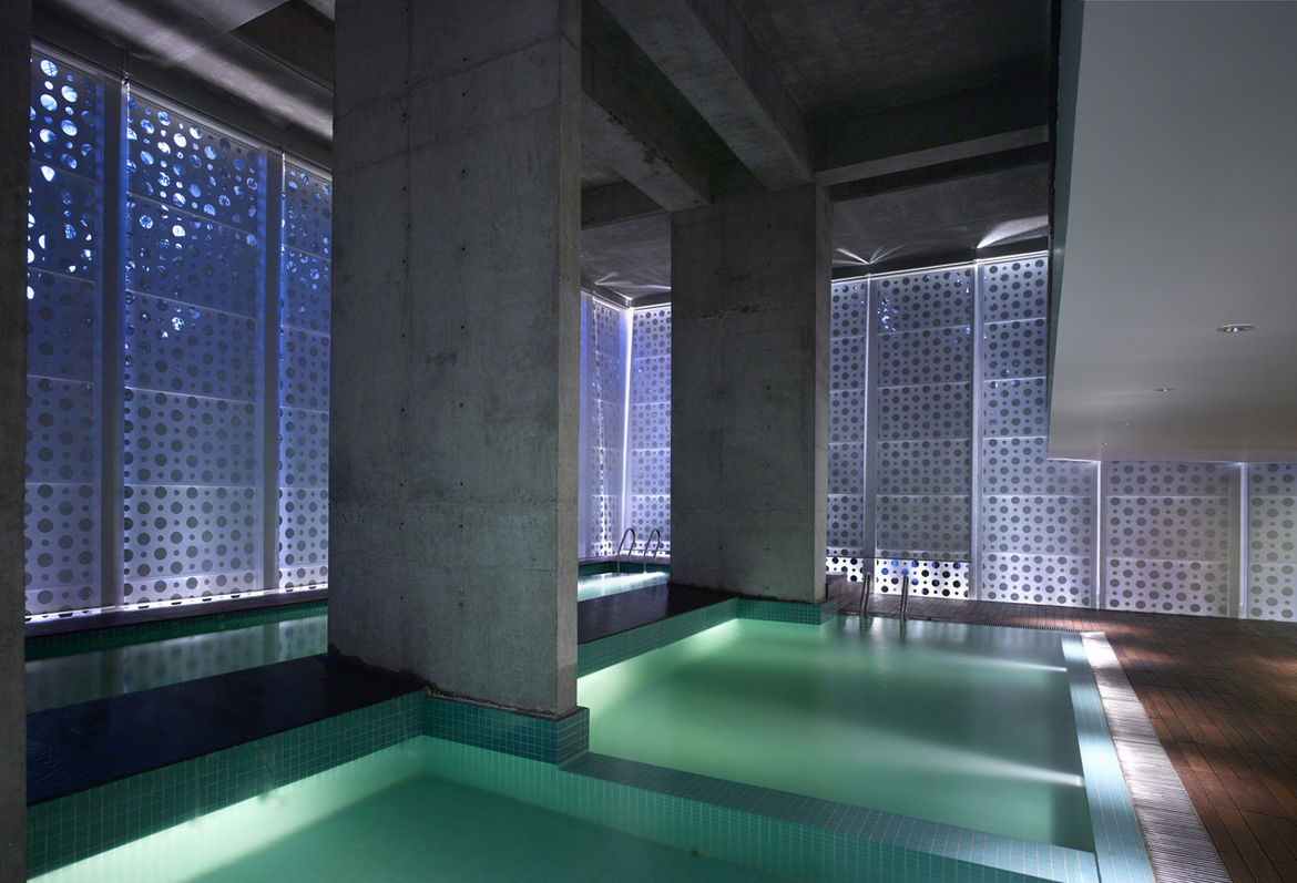 """An interplay of geometries in what Khanna calls """"the belly of the building."""" Uplights create new angles of light, raw concrete retains a rough edge and square pool tiles add texture and color while offsetting the perforated circles. The dropped ceiling at"""