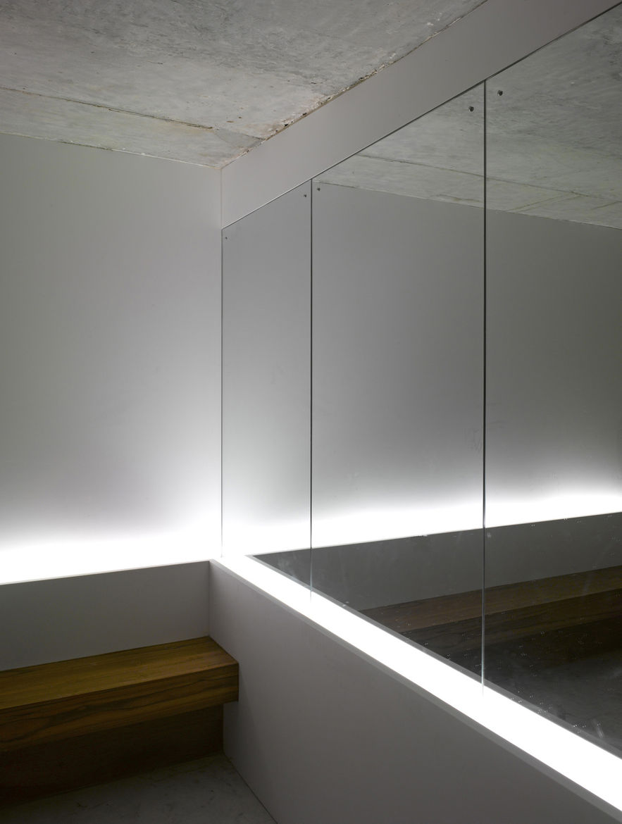 "<p>A mirror near the mailboxes in the lobby gives the illusion of more space. A team from <a href=""http://www.lighting.co.jp"">Lighting Planners Associates</a>, based in Japan, added the uplights behind the bench for effect. The architectural firm left the"