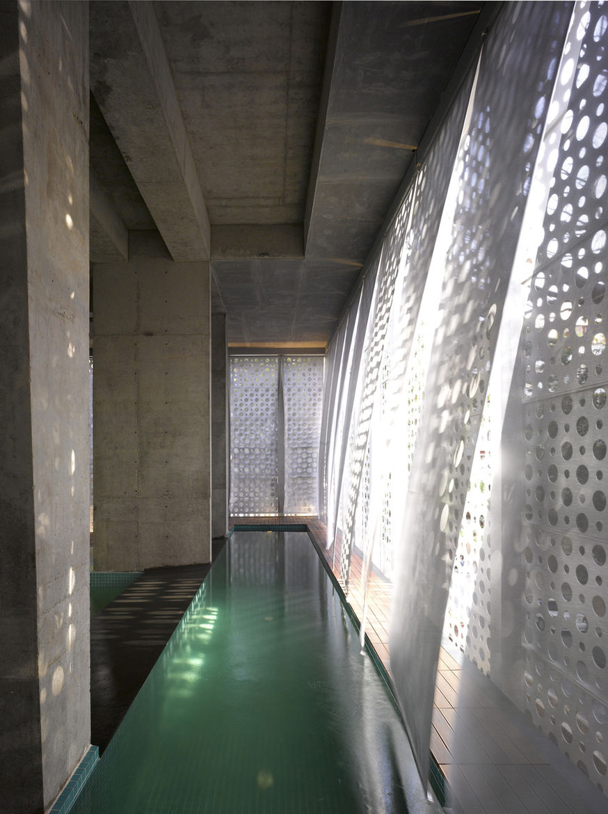 The pull-down scrims over the lap pool move with the breeze within the public space.