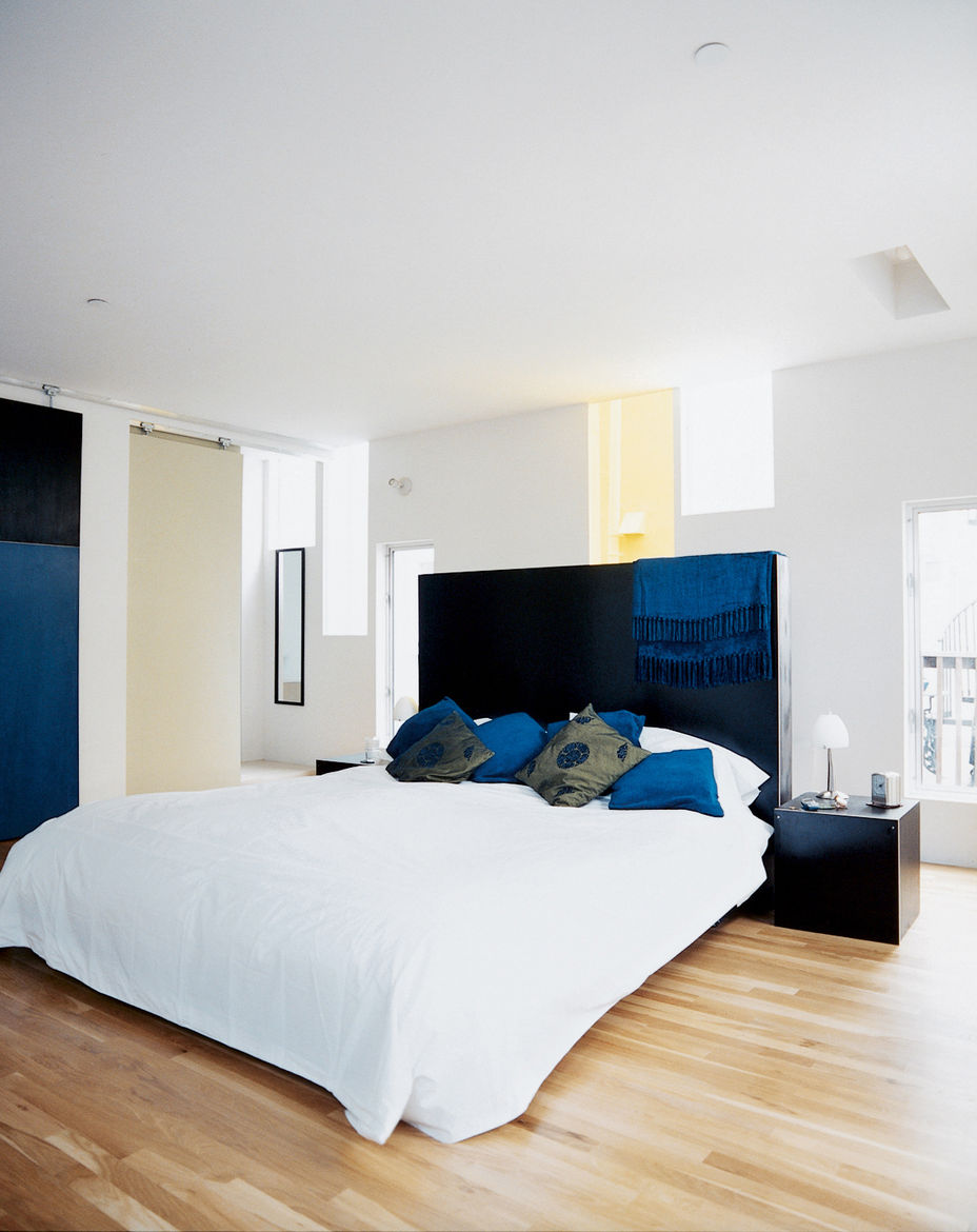 The narrow windows flood the master bedroom with light, while providing privacy. The dark-stained woods of the custom headboard and nightstands, all designed by the architect and built by Solicraft, cohesively tie the furnishings to elements like the bedr