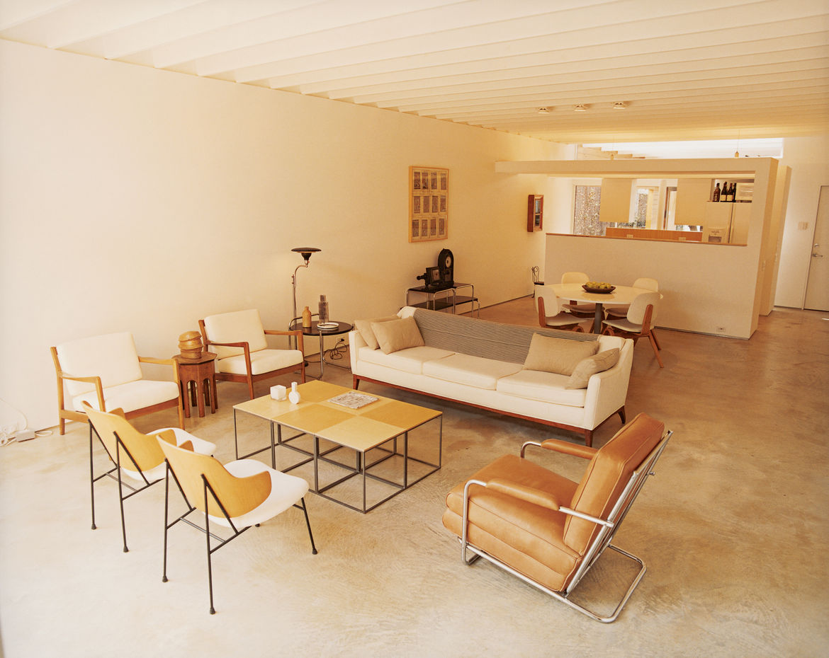 The living room of Baum's 1650-square-foot home features a poured-concrete floor as well as many vintage finds and artifacts from his travels. The sidechairs in the foreground are by Ib Kofod-Larsen and the leather chair is by Gilbert Rohde.