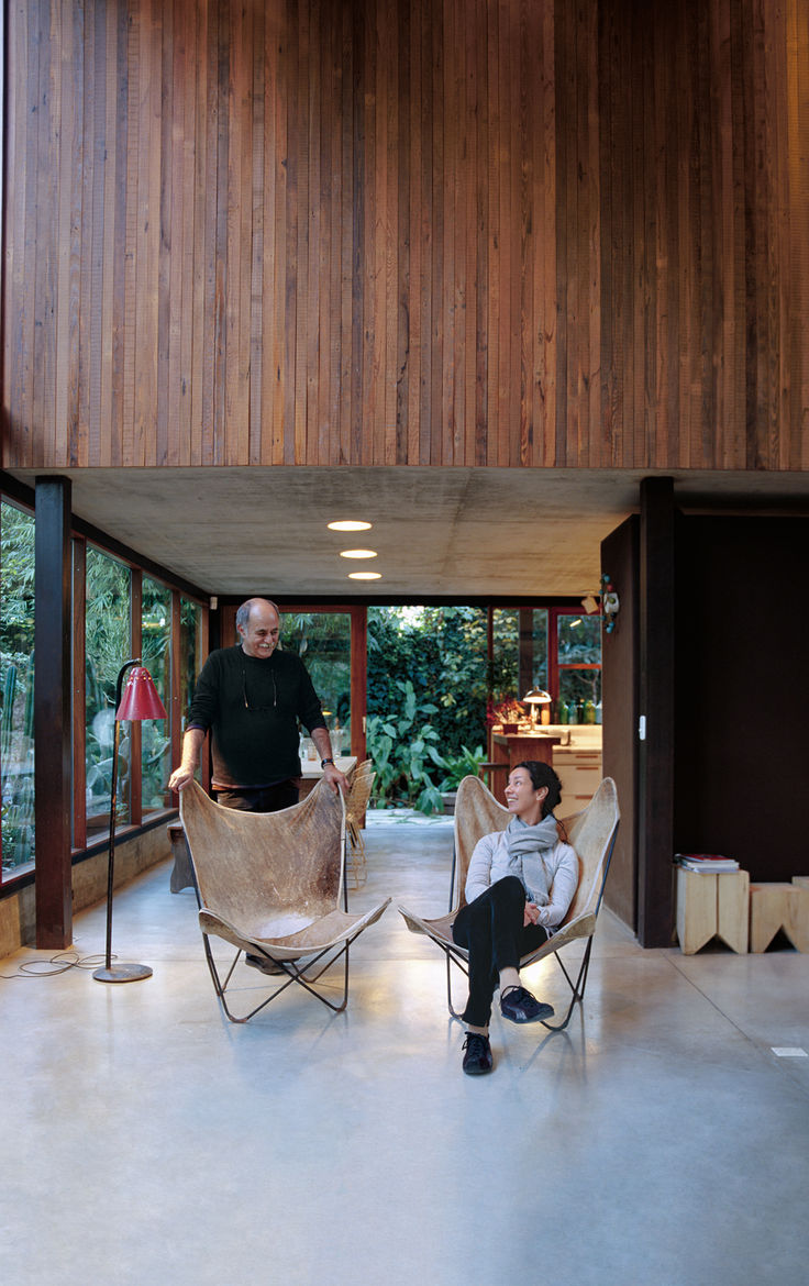 Sticotti and Hernaez relax in their living room, where custom-built windows and sliding doors enhance the indoor-outdoor effect.
