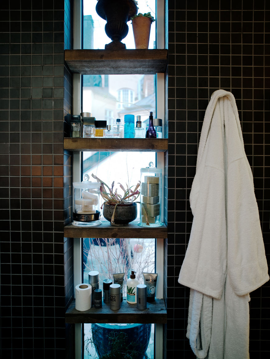 """In the bathroom, wooden shelves in front of the window screen the room from public view, and provide added storage. Photo by <a href=""""http://www.permagnuspersson.com/"""">Per Magnus Persson</a>."""
