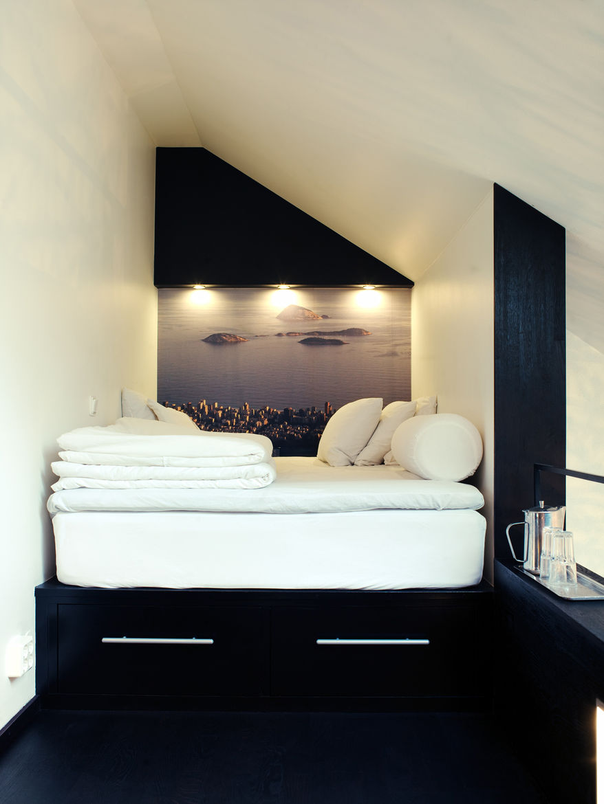 In the tiny sleeping loft is platform bed with two drawers beneath it. In place of wallpaper, Schonning enlarged a photograph he snapped in Rio de Janeiro. The inset spotlights and a small shelf at the end of the bed offer light and additional storage. Ph