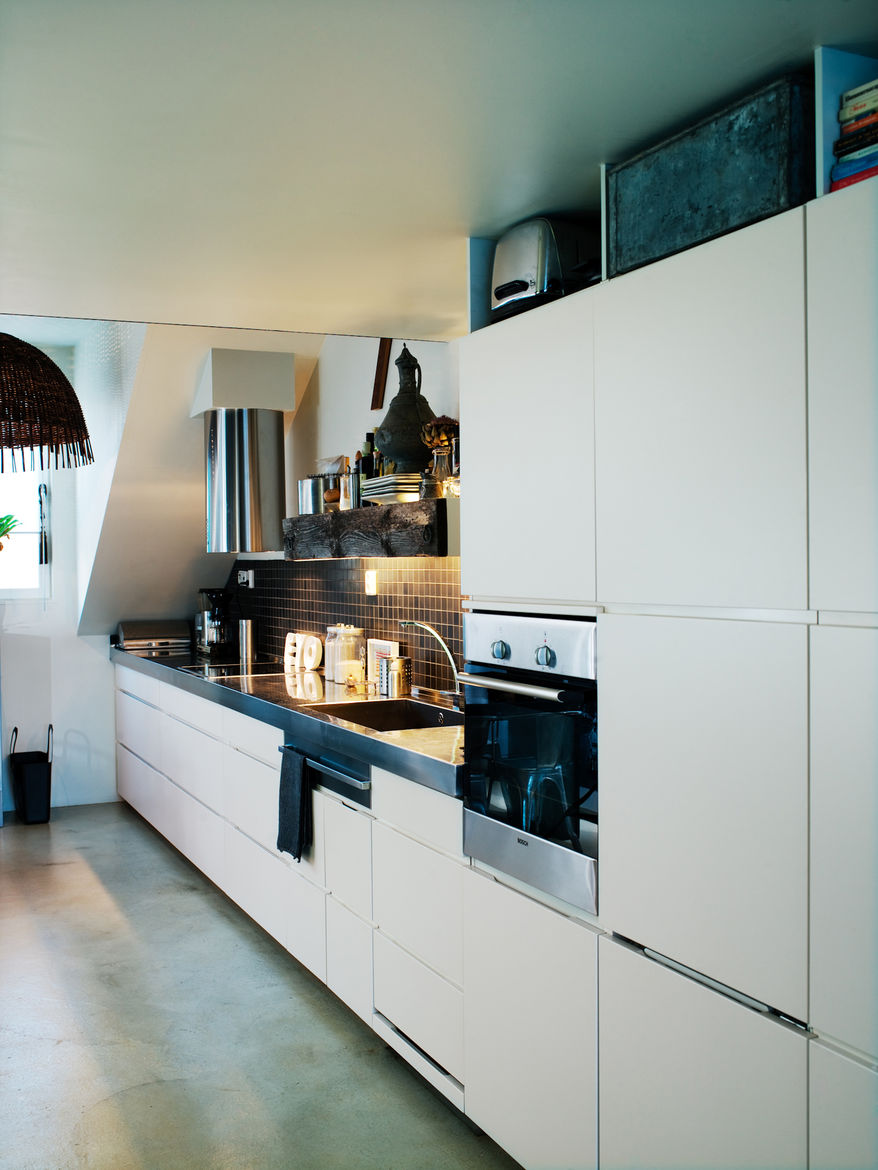"""The kitchen wall has a built-in fridge, freezer and dishwasher. Photo by <a href=""""http://www.permagnuspersson.com/"""">Per Magnus Persson</a>."""