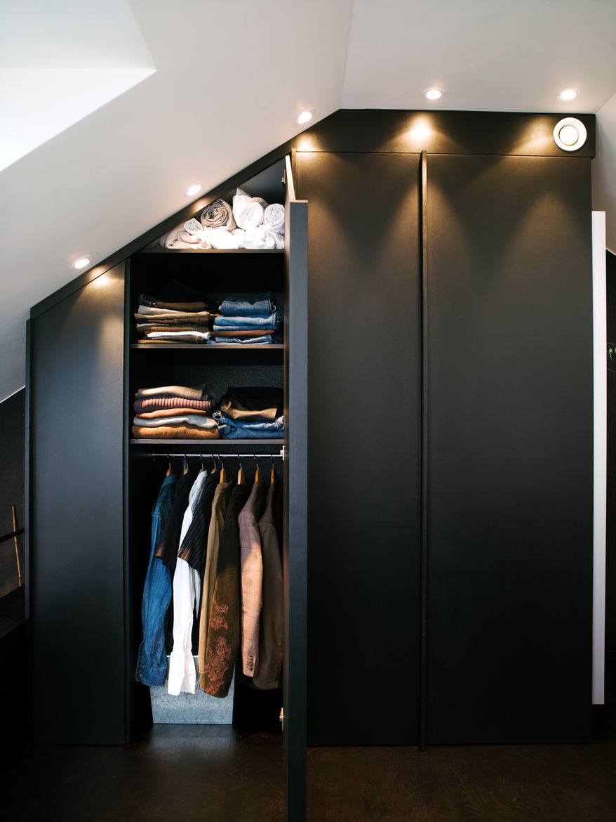 """The apartment's built-in closets are deep and have mirrors on one side. Spotlights set flush overhead provide light and also allow the maximum amount of storage, all the way to the ceiling. Photo by <a href=""""http://www.permagnuspersson.com/"""">Per Magnus Pe"""