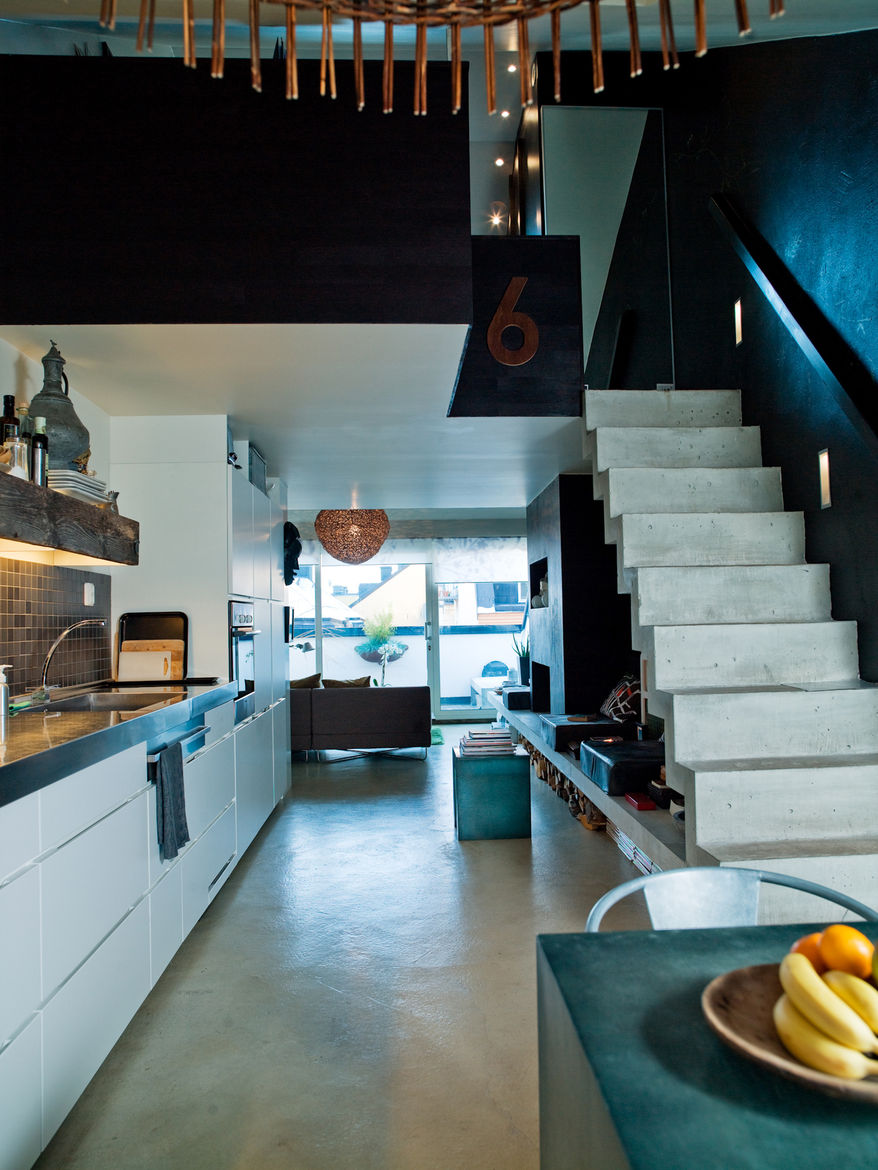 """Back downstairs, the kitchen occupies a long wall. The stainless steel worktop was so long—more than 16 feet—that it had to be lifted in through the window. Photo by <a href=""""http://www.permagnuspersson.com/"""">Per Magnus Persson</a>."""