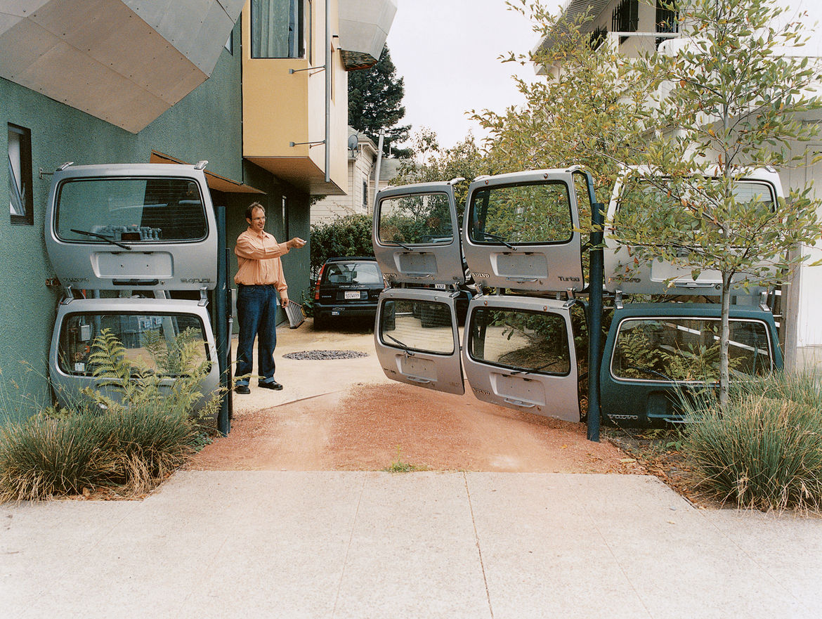 """Karl Wanaselja, with clicker in hand, redefines """"gated community."""" Acting as the contractor, he worked closely with a gate fabricator to assemble the unusual entrance. """"I wanted to find an orange one,"""" he says, referring to the Volvo hatches, """"but finding"""