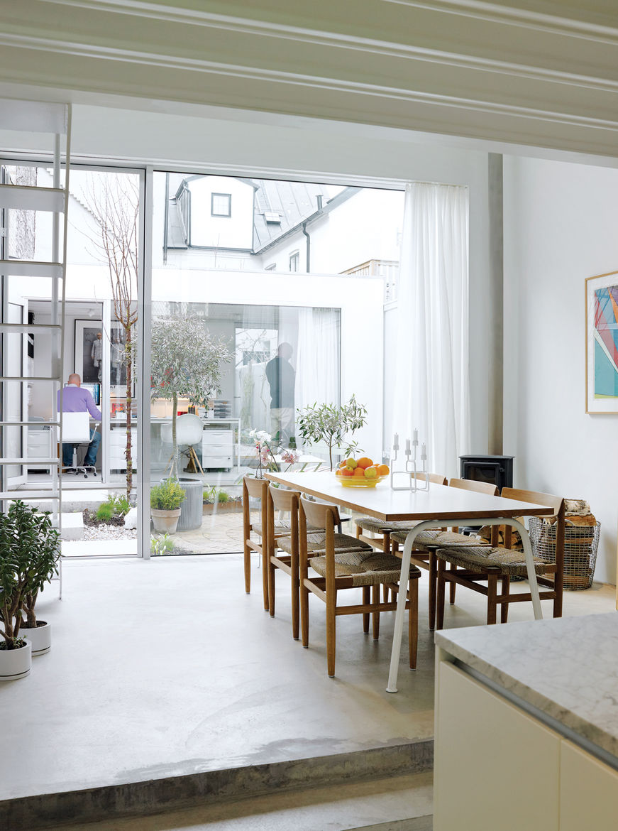 The view from the kitchen is as lively as it is light, taking in the dining area, tiny courtyard garden, and the separate office building backed by the jumble of old buildings to the rear. The rustic dining chairs are by Börge Mogensen from Karl Andersson