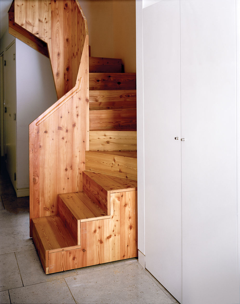 The staircase is a bespoke design by Luke Tozer, made of a larch composite sourced from sustainable forestry in Austria. It was made off-site and then assembled in position like a jigsaw puzzle.