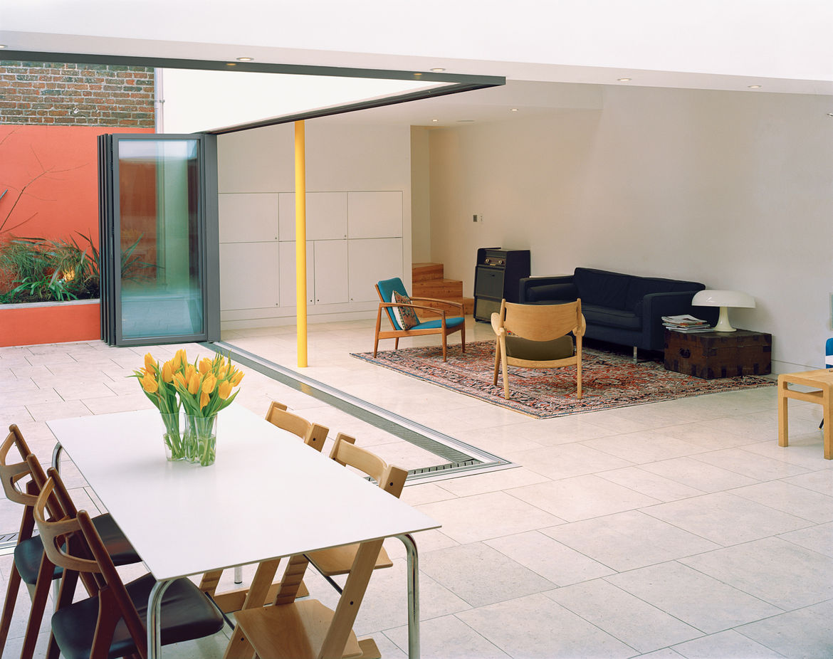 The glass wall separating the main living area and the inner courtyard garden opens like an accordion to create a barrier-free transition. Built-in planters along the walls of the courtyard add greenery without eating into the valuable surface  area of th