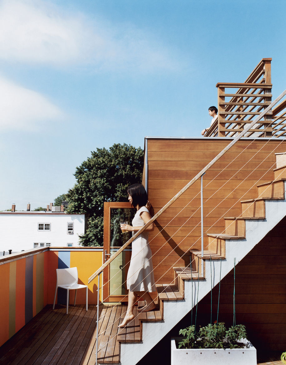 Jinhee and John, looking east from the dual-story roof deck. The door behind Jinhee leads to the top floor of Andy Hong's unit, where a bar fridge contains wine ready for parties. In the background is the boxy form of a traditional triple-decker.