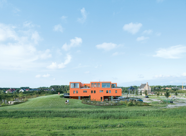 Seen here from the south, Villa van Vijven's orange facade is meant to mimic the tiled rooftops of Holland's country buildings, while the building's horizontal pull echoes the flat landscape. The second-floor living rooms look out on the 4,200-square-foot