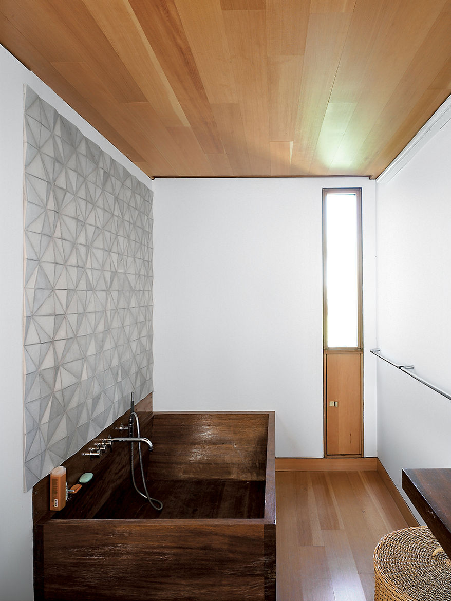 In the bathroom, a custom ceramic backsplash designed by Meredith and Sample joins an iroko-wood tub created by their students a the University of Toronto.