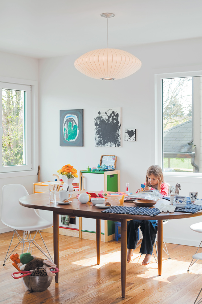 Daughter Zoë finds a cozy spot at the dining-room table, by Dux, seated on an Eames Molded Plastic chair and under a George Nelson Saucer lamp.